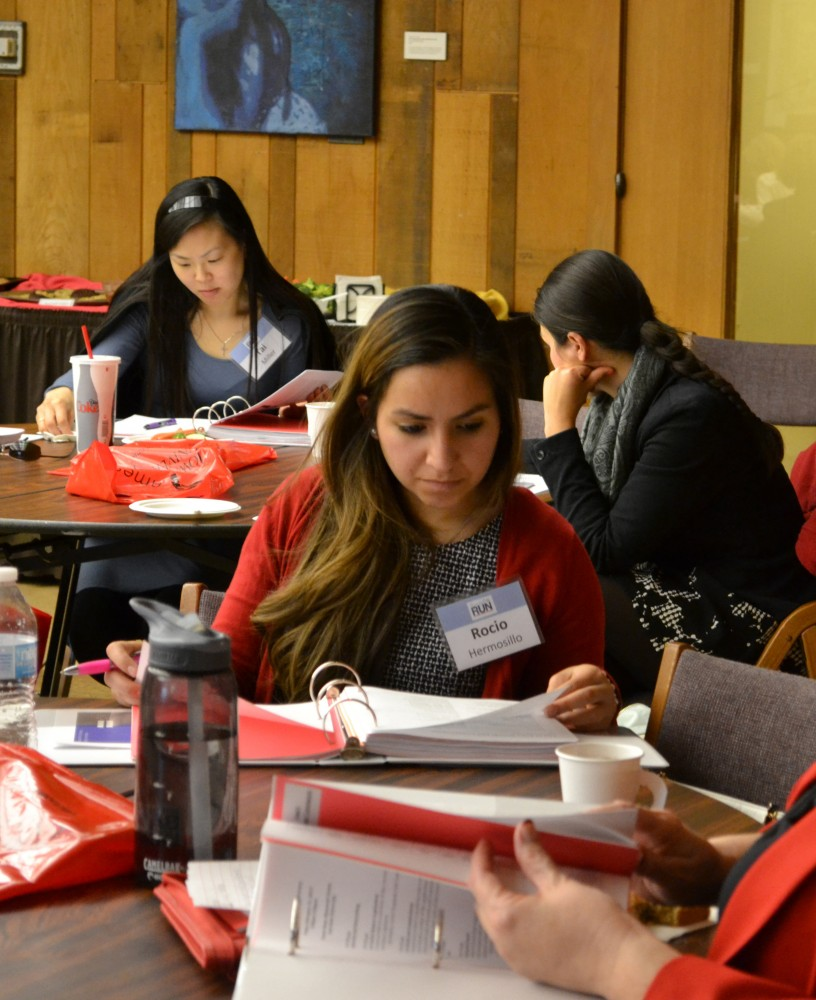 Tai Miller (left) and Rocio Hermosillo (front) browse workshop materials on Feb. 13.
