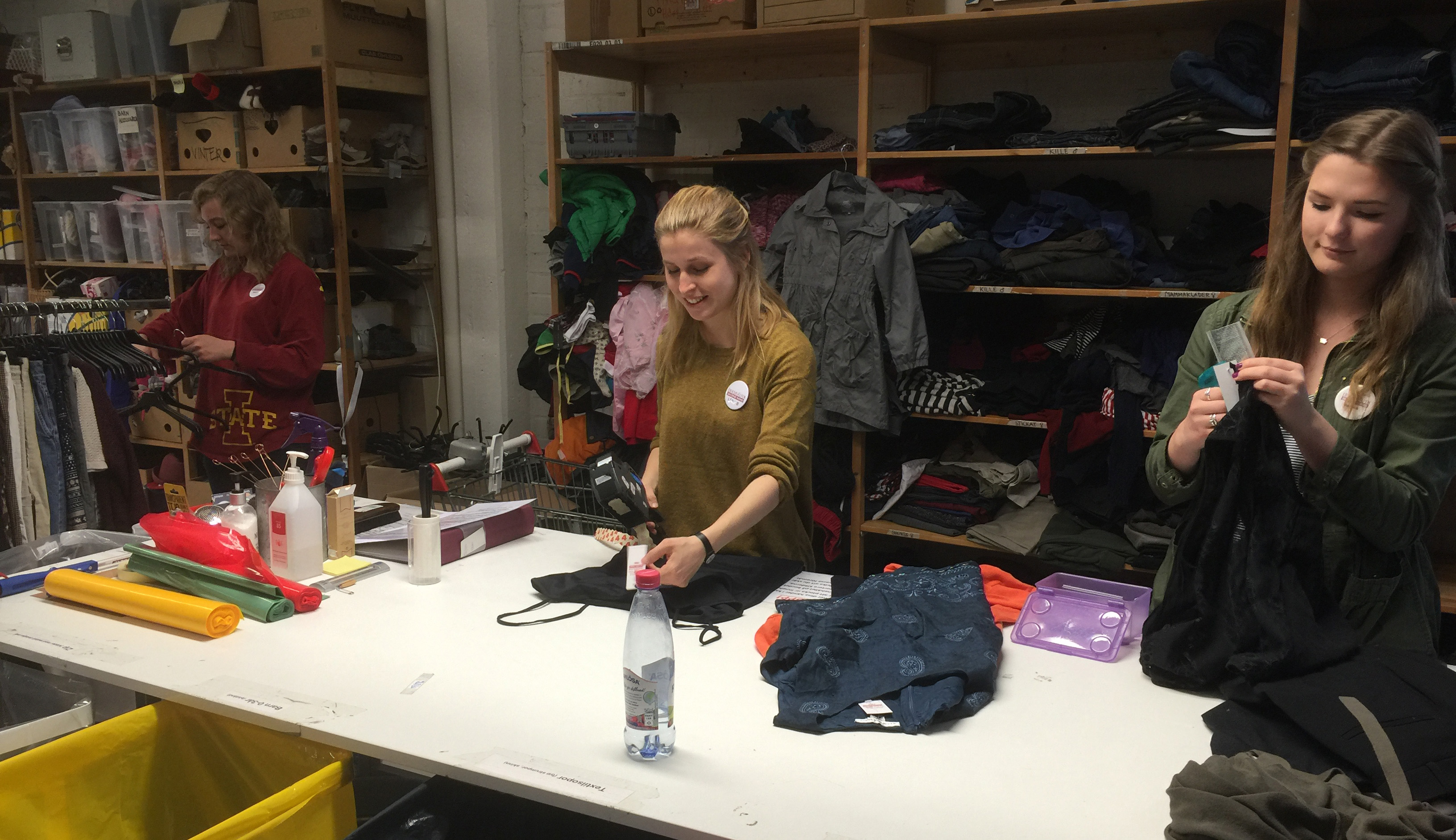 Student volunteers Emma Grace Reese (left) and Emma Bruen (right) work with a staff member at Erikshjälpen Second Hand.