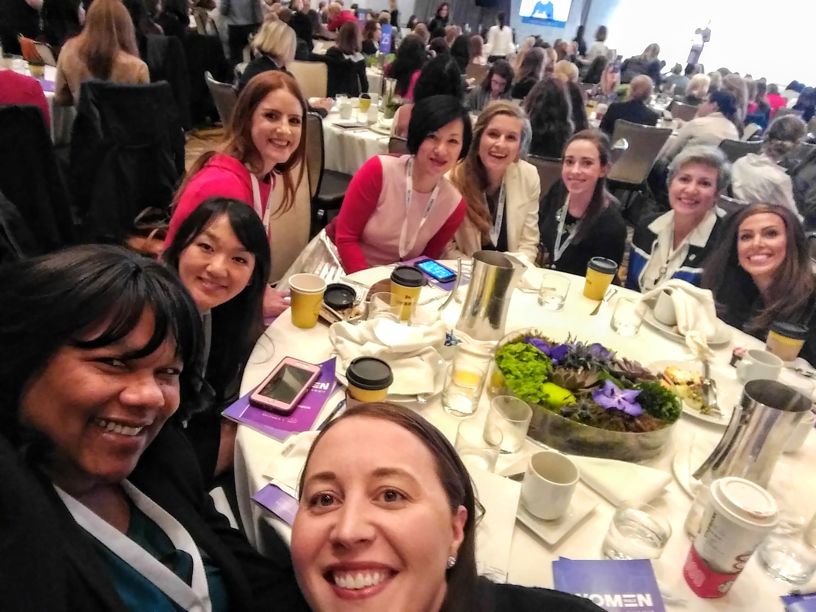 Monic Behnken, far left, takes a picture of her table during the POLITICO Women Rule Summit on Dec. 5.