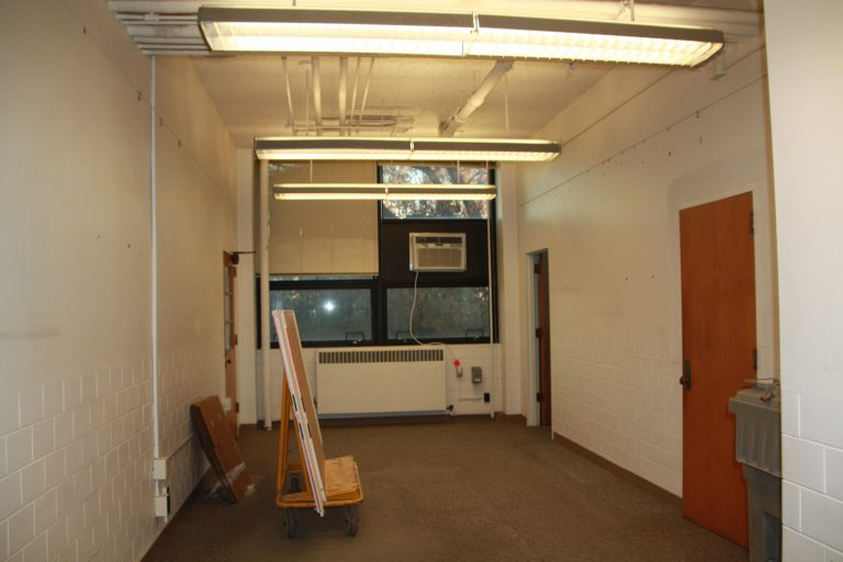 Existing office with furniture and wall decorations removed.