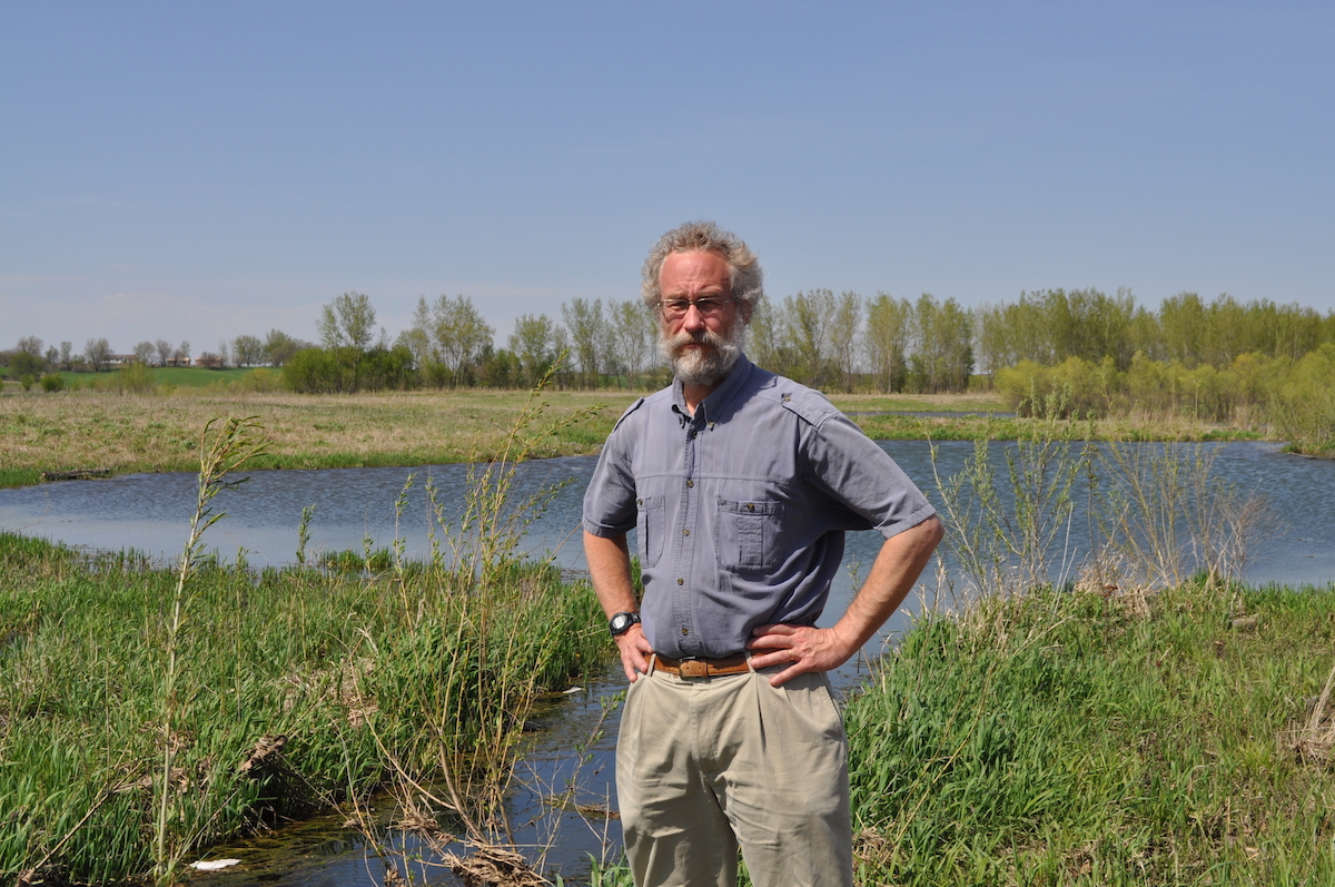 Dr. William Gutowski standing in the foreground. A small pond appears in the middle ground. Trees and houses in the distant backbround.