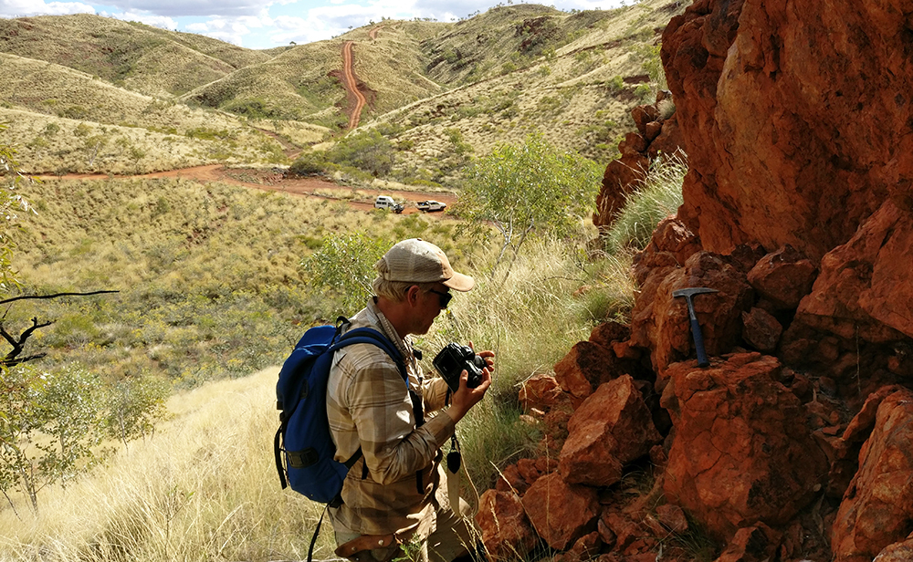 Benjamin Johnson of Iowa State University woks at an outcrop in remote Western Australia where geologists are studying 3.2-billion-year-old ocean crust.