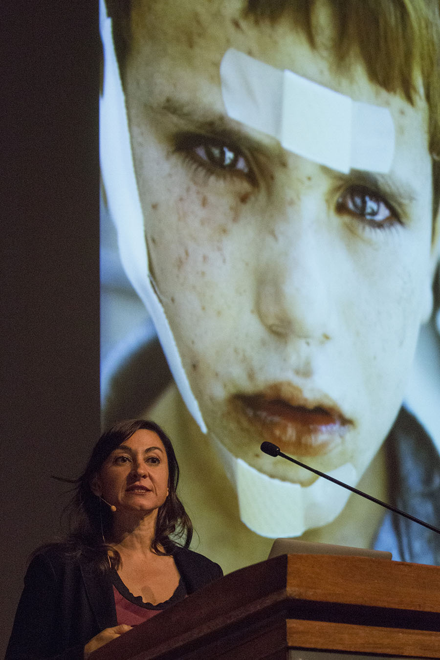 Lynsey Addario at the podium with her photo of an injured boy behind her.