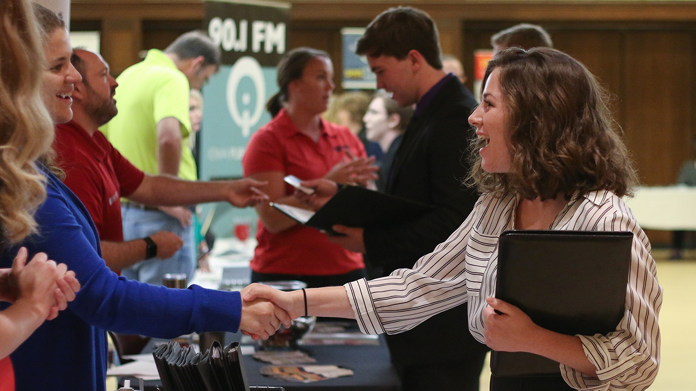 Female student shakes hands with employers at career fair