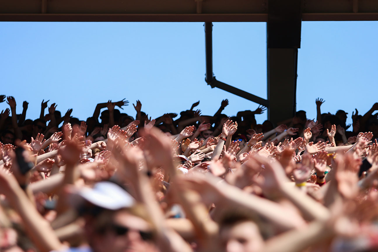 fans celebrate with hands in the air at a football game