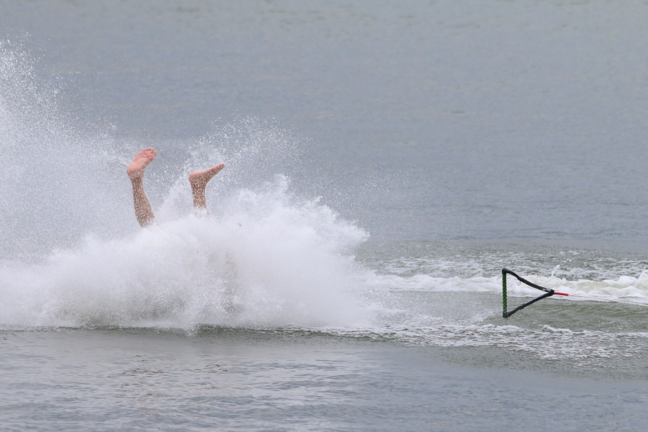 a water skier takes a tumble in a lake