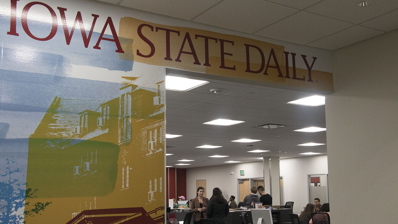 photo of Daily newsroom with logo in foreground and students in background