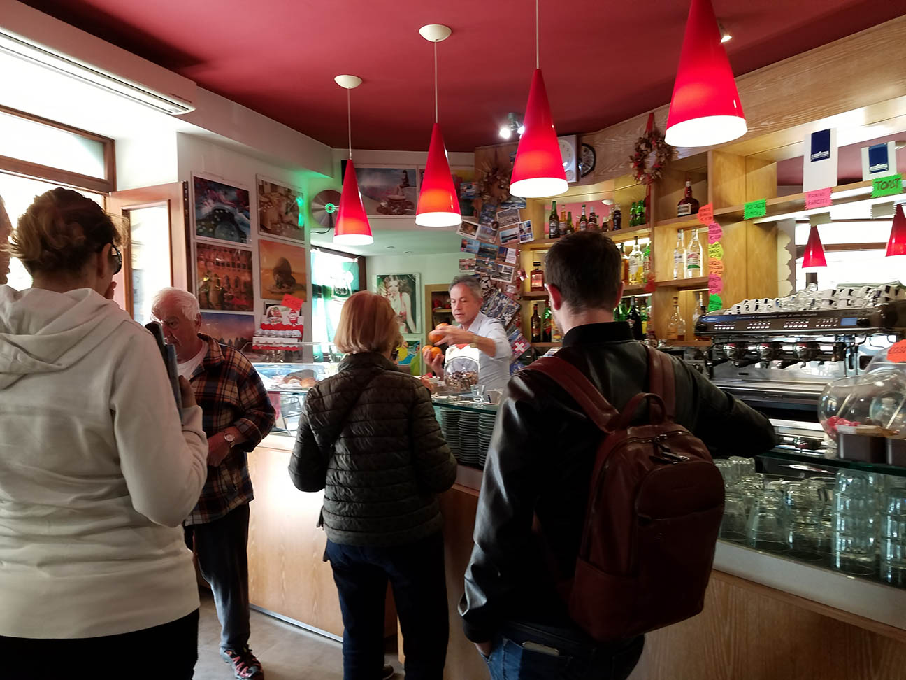 Mario, the owner of Mama's Café in Urbino, Italy, whips up several customers