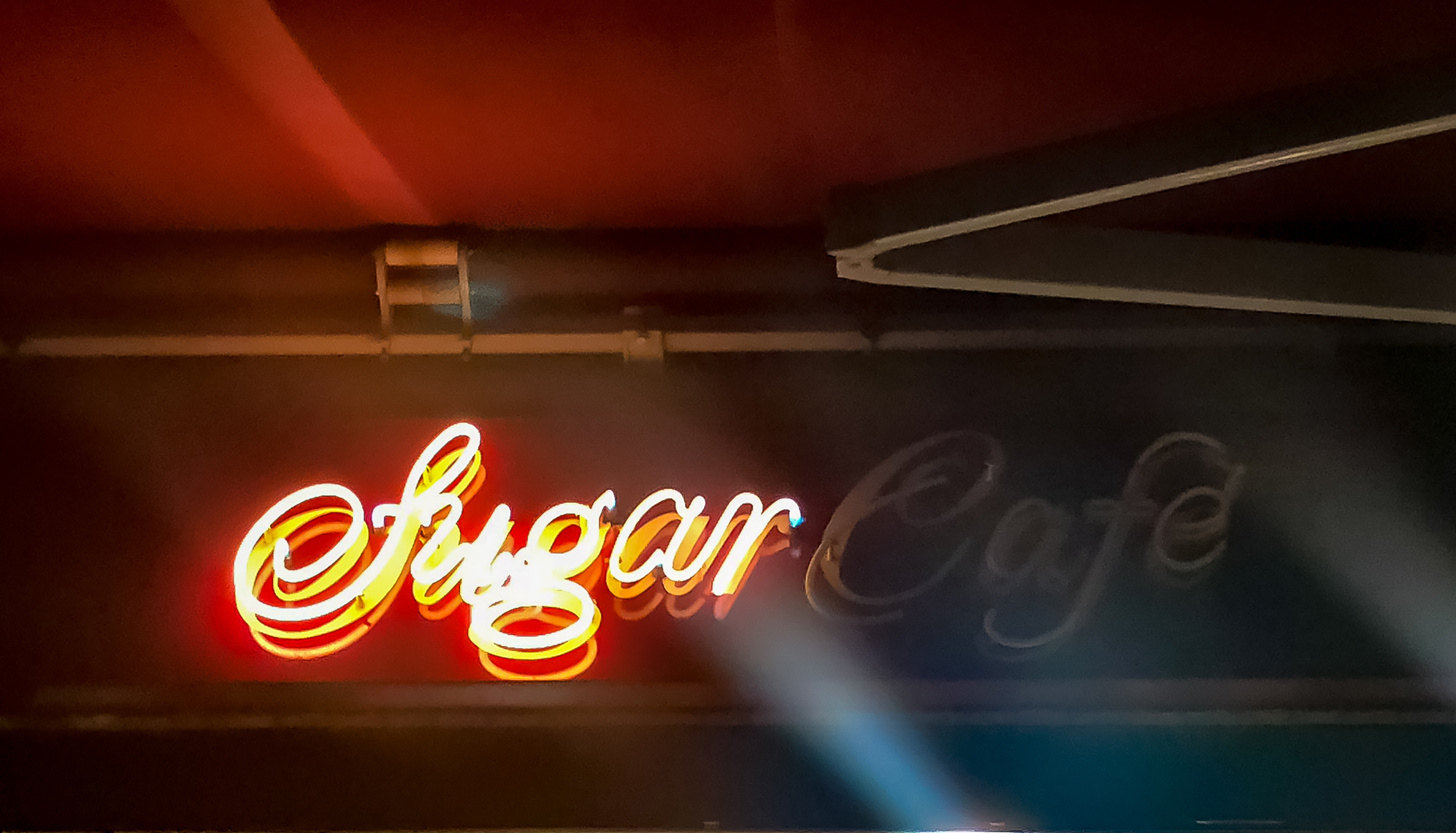 A neon sign reading Sugar Cafe