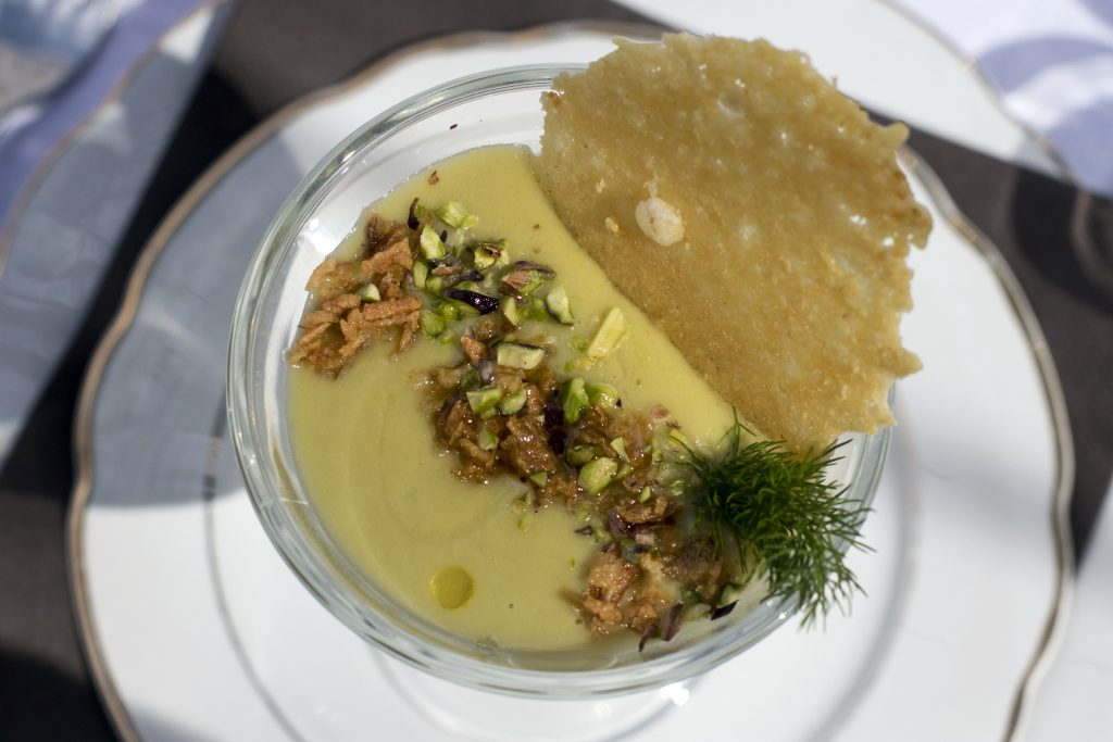 a bowl of soup with pistachio and parmesan garnish