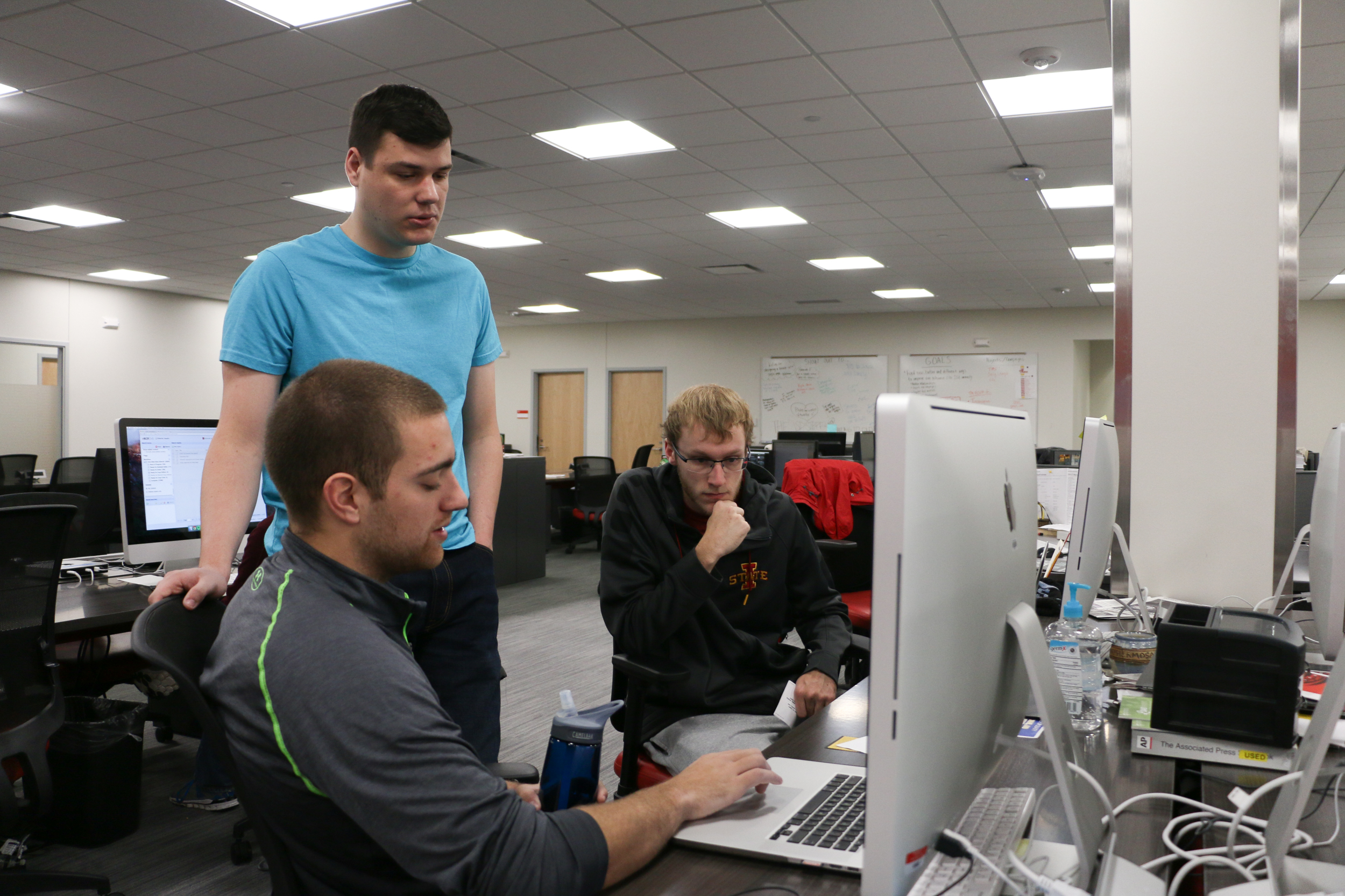 Assistant Sports Editor Ryan Young, Sports Editor Luke Manderfeld and a reporter work in the Daily's new Campustown office. Photo by Emily Blobaum/Iowa State Daily