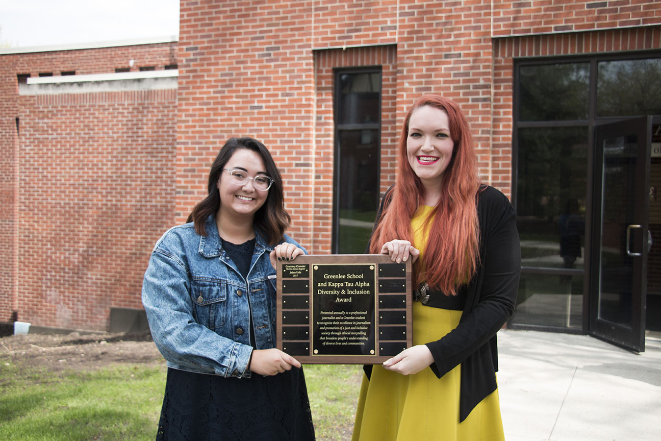 two women stand with plaque.