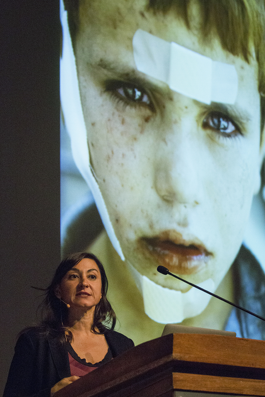 Lynsey Addario stands at the podium with one of her images of a young boy with bandages on the projector screen behind her