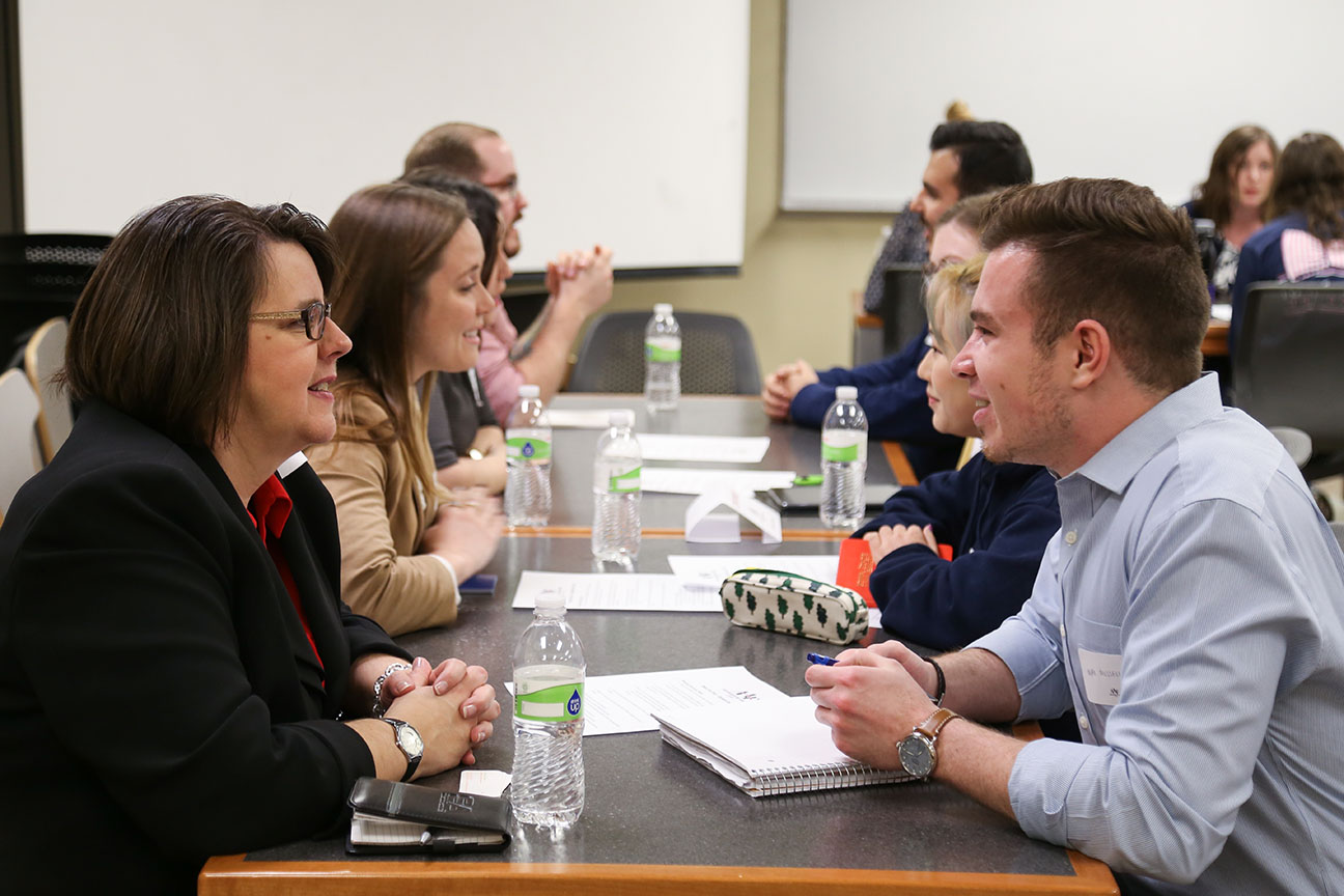 students and professional network across the table in Hamilton Hall