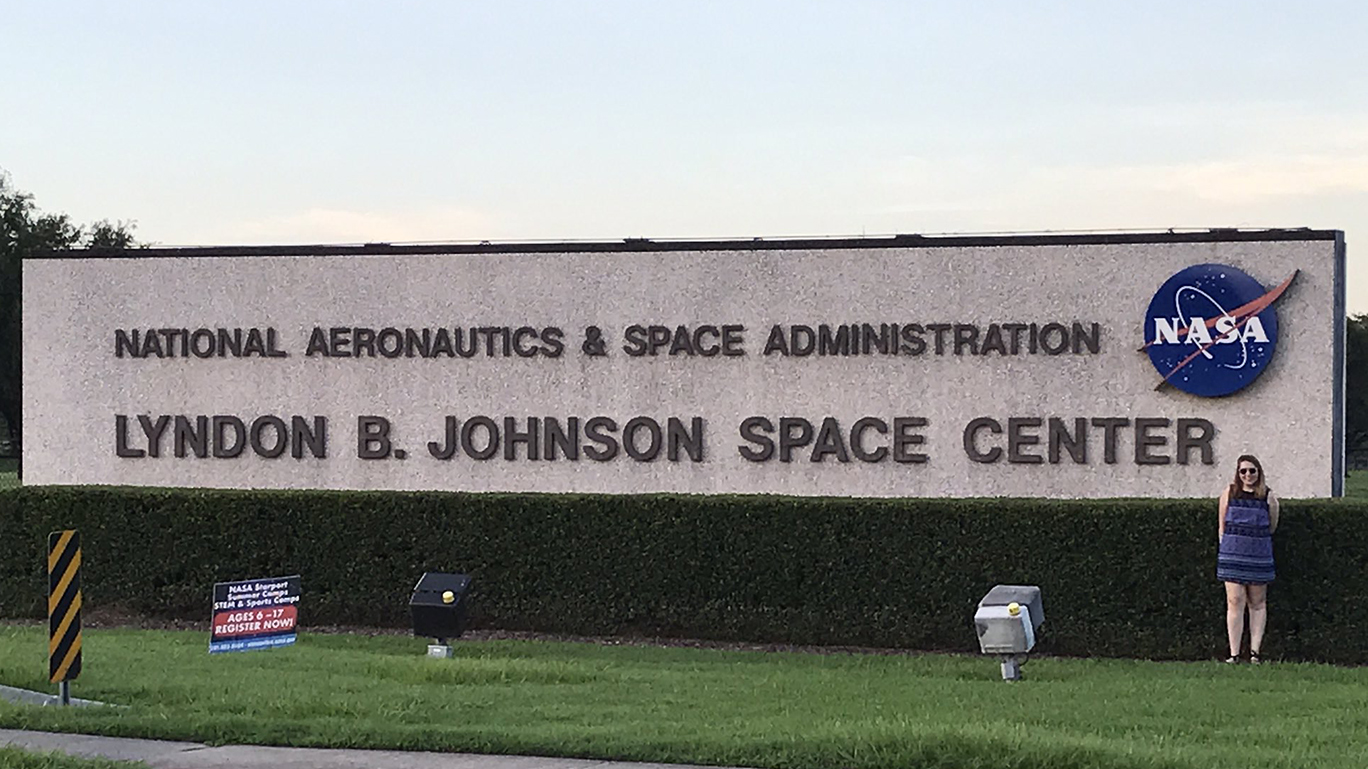 a female student stands in front of the NASA sign at Lyndon B. Johnson Space Center