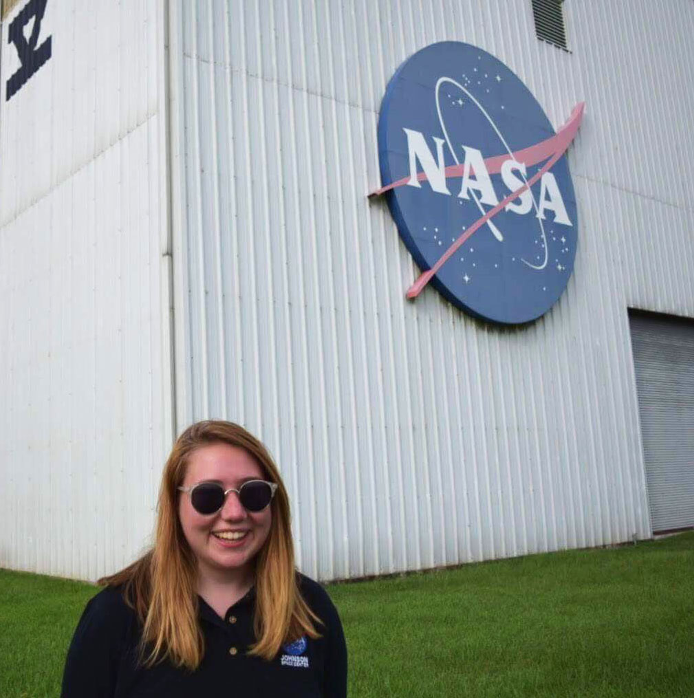 Madison stands in front of NASA sign