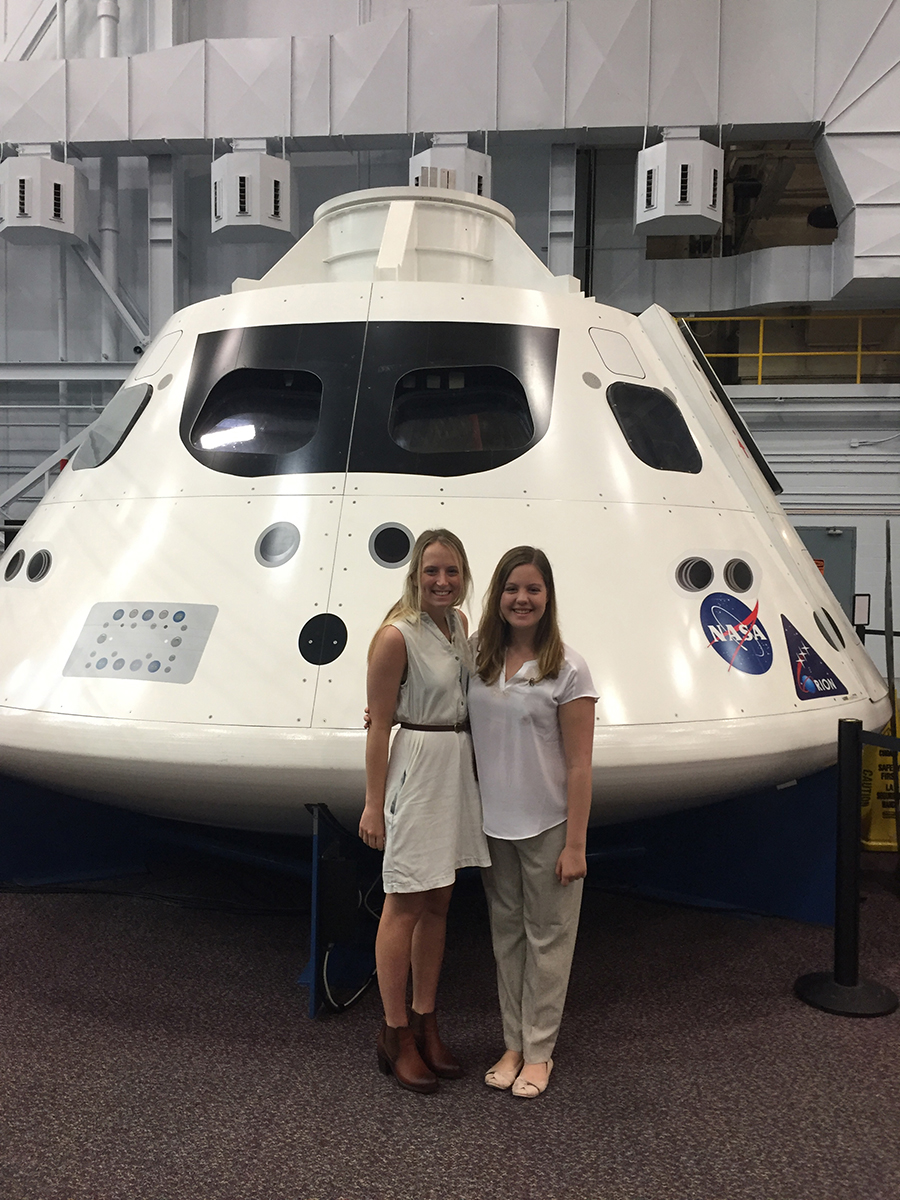 two women stand in front of space shuttle mockup