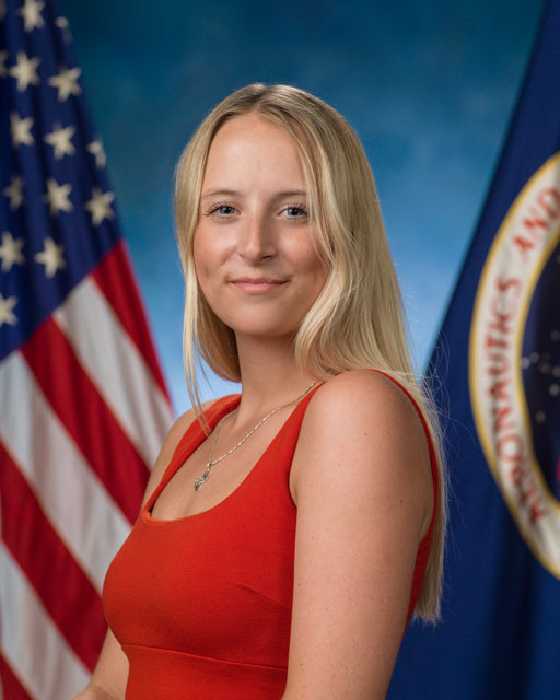 woman in red dress with American and NASA flags behind her