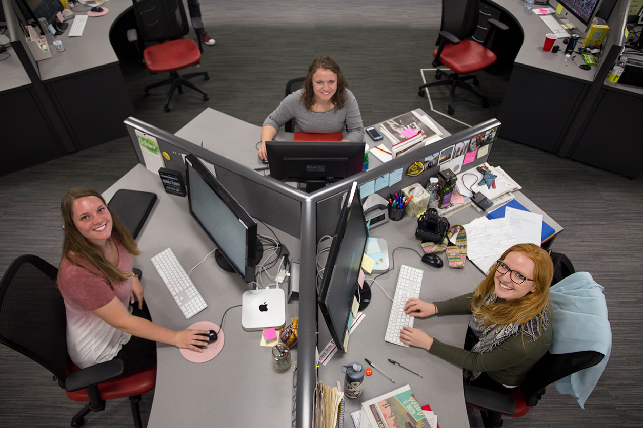 Three female students sit at their pod of three desks at the Iowa State Daily office.