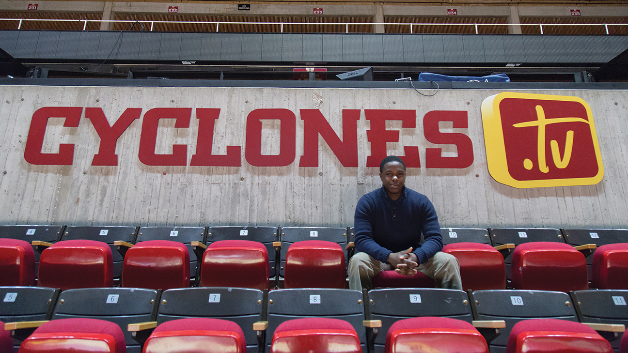 Lester Mwirichia sits in the stands at Hilton Coliseum in front of the Cyclones.TV sign.