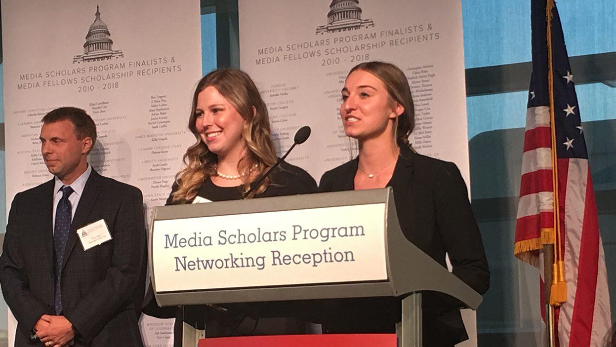 Ashley Kirkpatrick and Lindsey Moor stand at podium