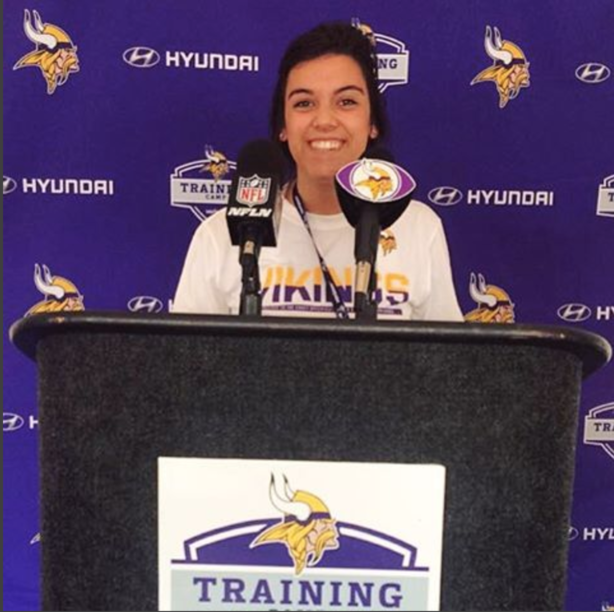 Emily poses at the Minnesota Vikings press podium during her internship.
