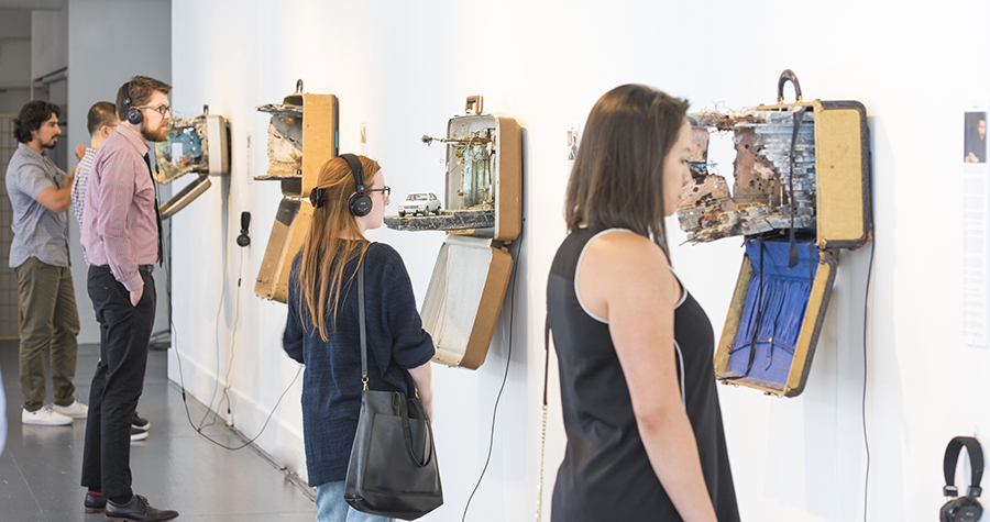 People looking at art inside of suitcases.