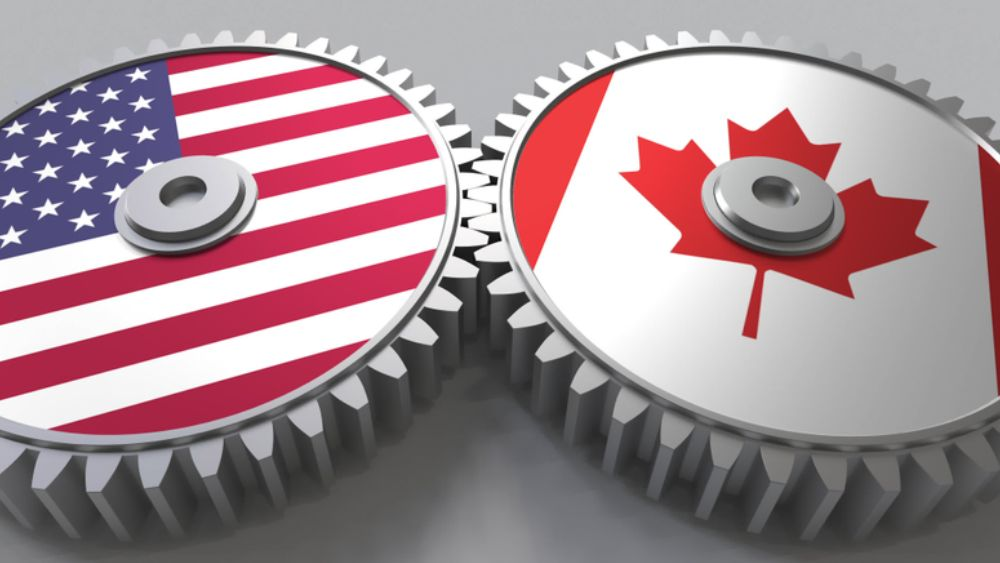 Two gears interacting, one with American flag and one with Canadian flag on the face of them.