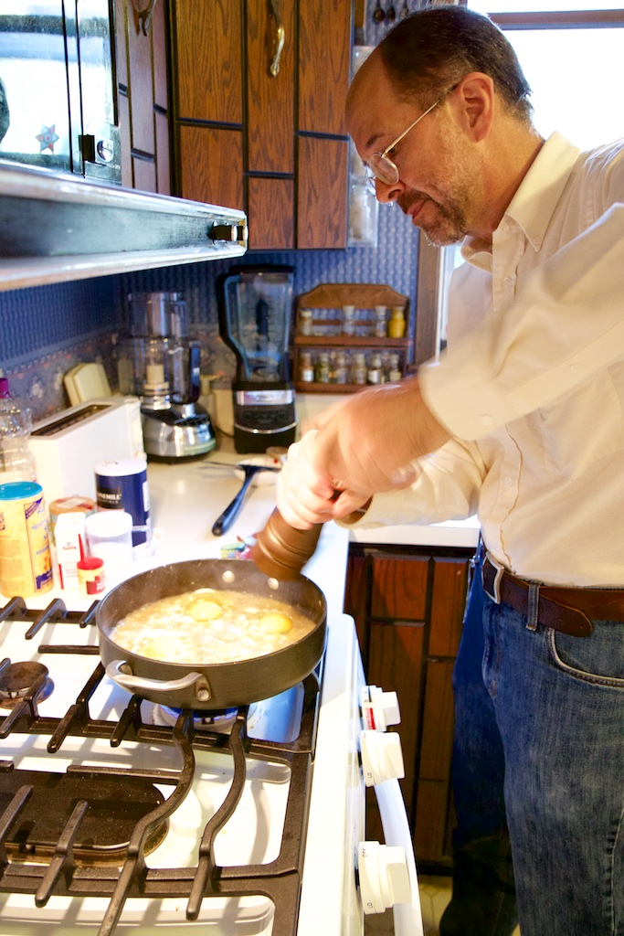 Paul Canfield stands at the stove putting salt into a dish in a large frying pan.