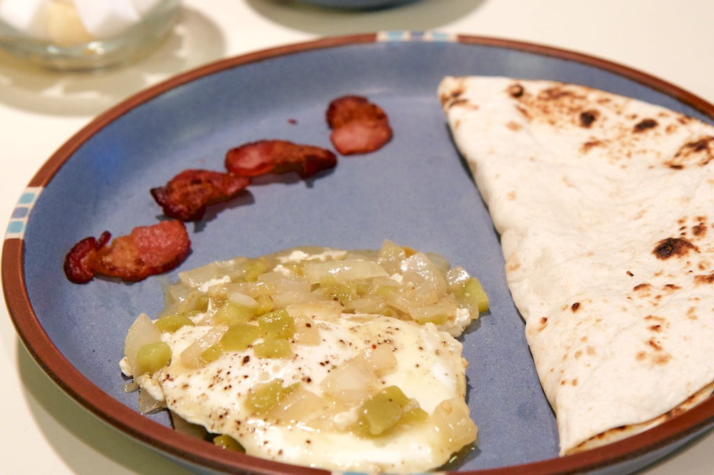 On a blue plate lies a tortilla folded in half, bits of bacon, and eggs with green chili.