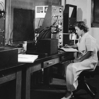 A black and white photo of Darleane Hoffman at a desk with various machines.