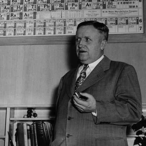 A black and white photo of Frank Spedding stnading in front of a periodic table and chemistry books.