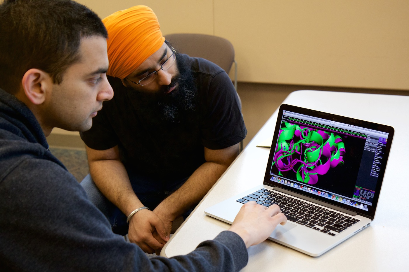 Jagannathan Alagurajan and Navjot Singh sit at a desk looking together at an image of an engineered protein on an apple laptop.