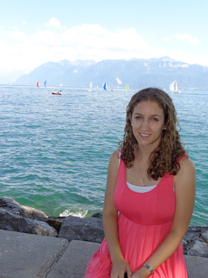 Katherine Wiegart sits on a rocky ledge area beside sea-blue water, with sailboats behind her and beyond the water, mountains.