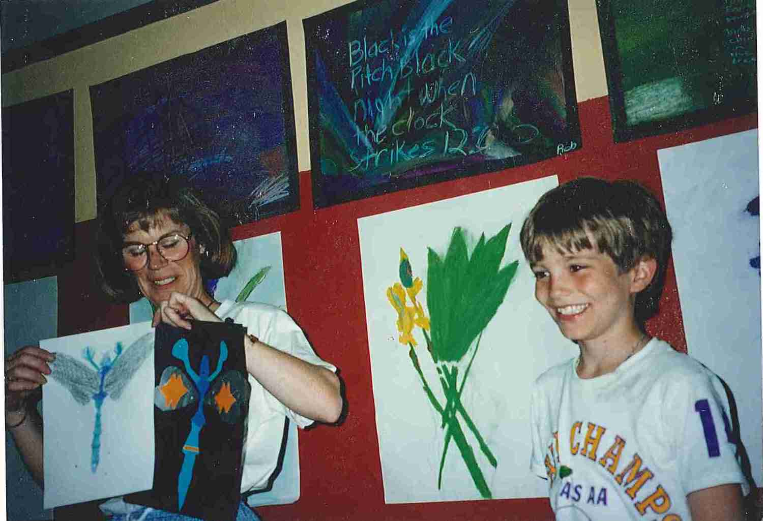 Rob Stupka in elementary school with his teacher holding drawings.