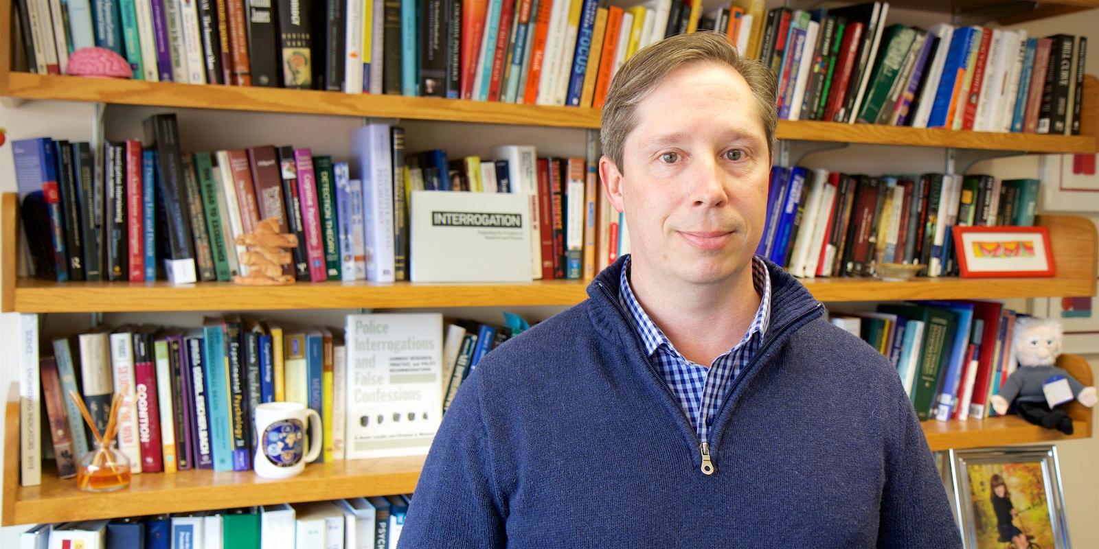 Chris Meissner poses in front of bookshelves.