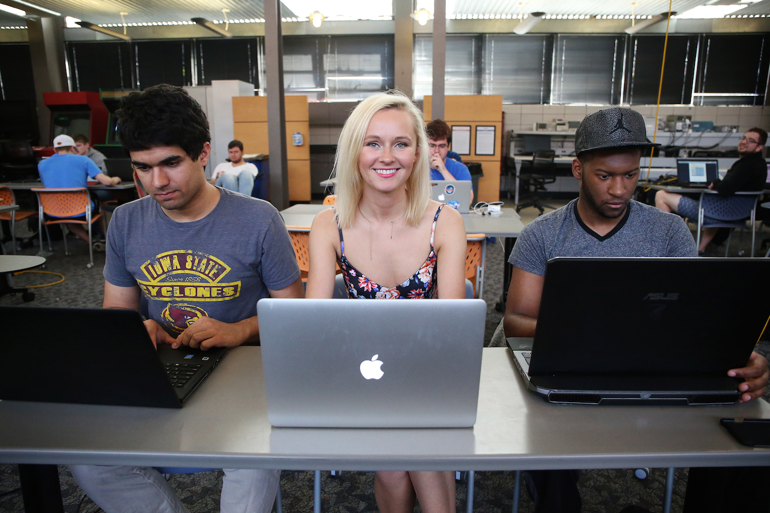 Kelsey Hrubes sits at her mac laptop between two men on their laptops.