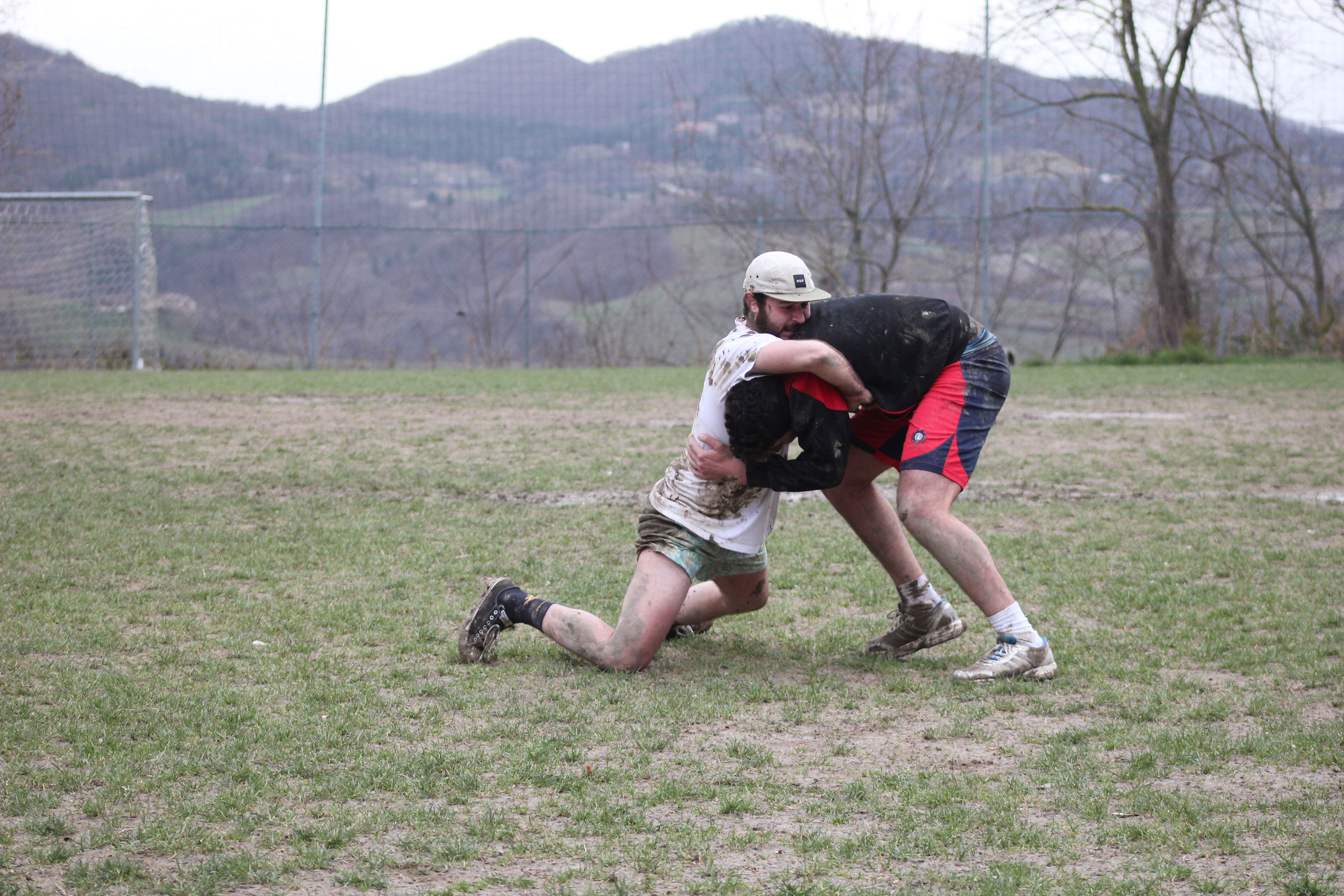 Two men wrestle on a field with hills in the background.