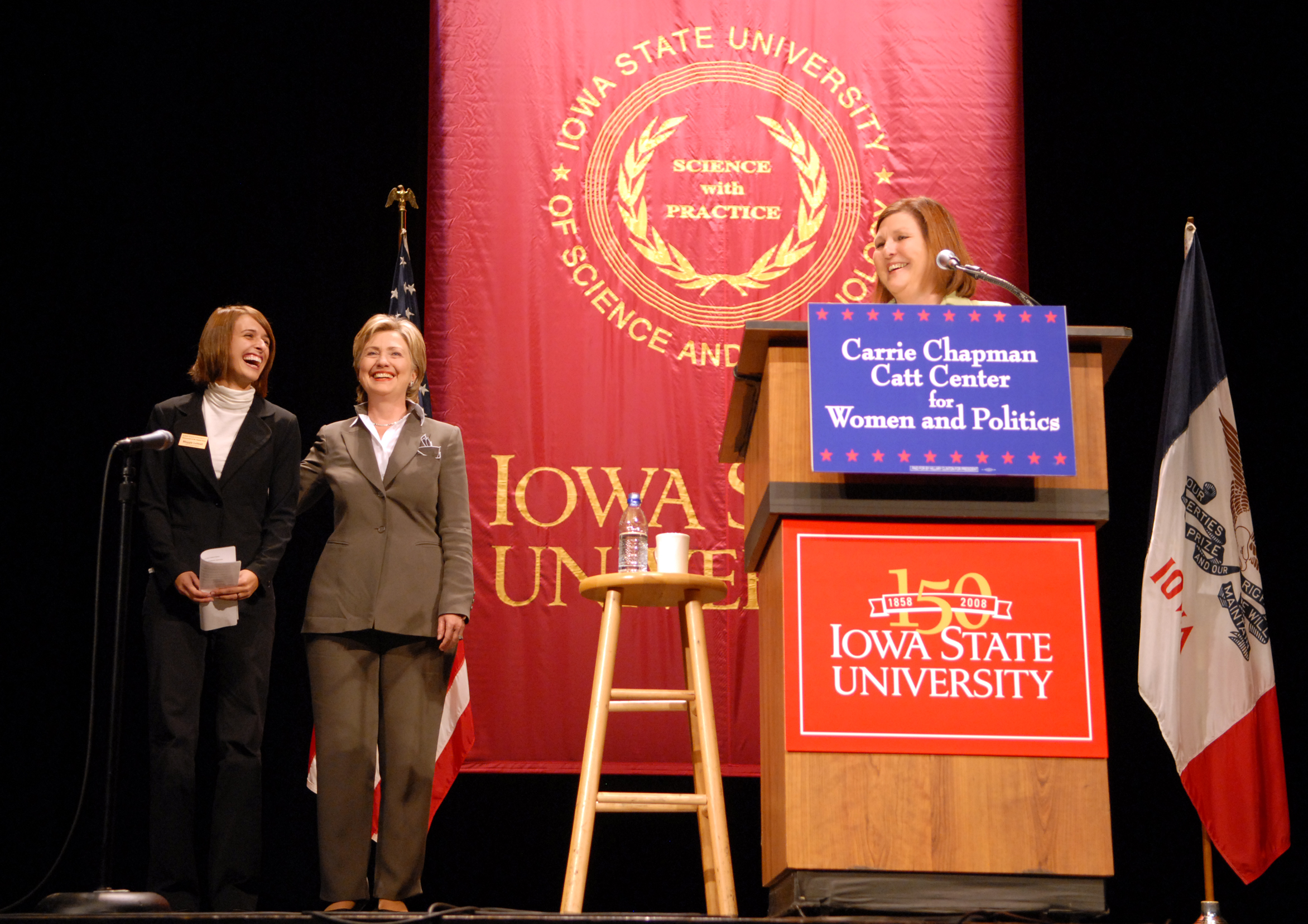 Dianne Bystrom speaks at a podium. Hillary Clinton and an Iowa State student stand next to the podium.