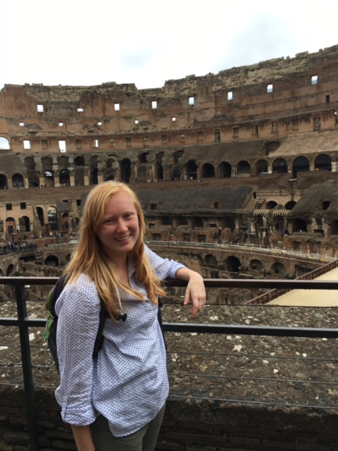 A student stands near a railing inside the Coliseum in Rome, Italy.