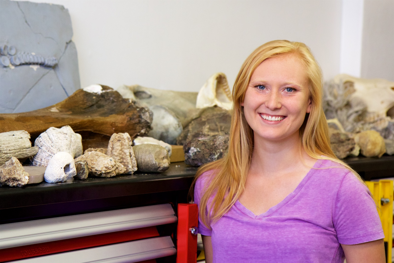 Portrait style photo of Brittany Grosskopf in front of geology samples.
