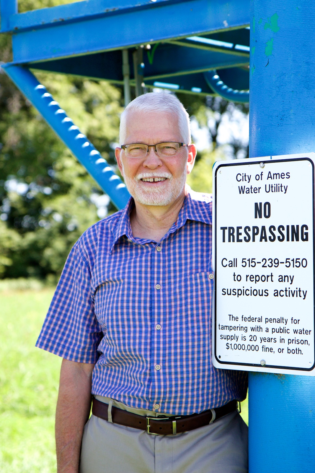 Portrait style photo of Bill Simpkins next to a water utility sign.