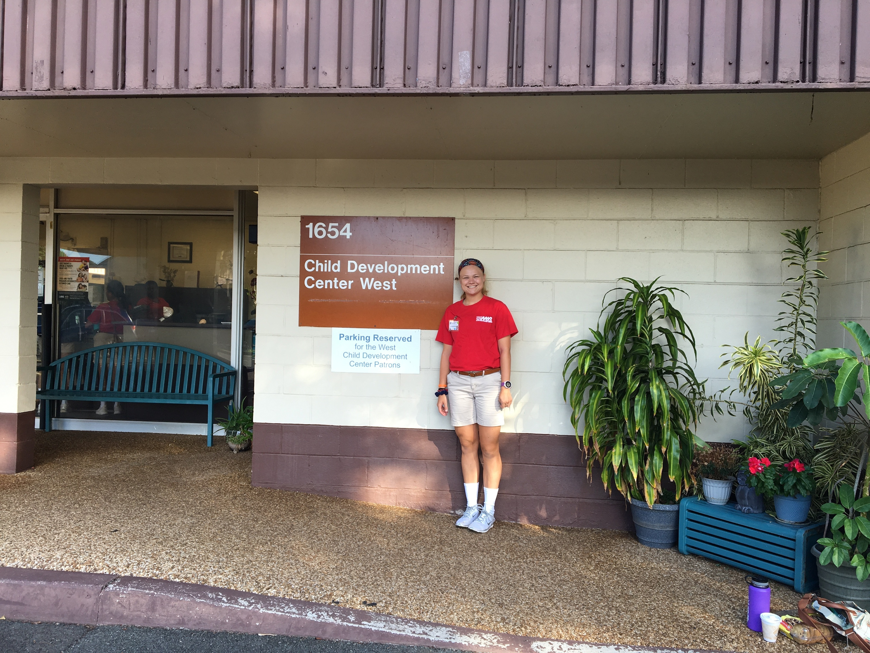 A student stands outside in front of a Child Development Center building.
