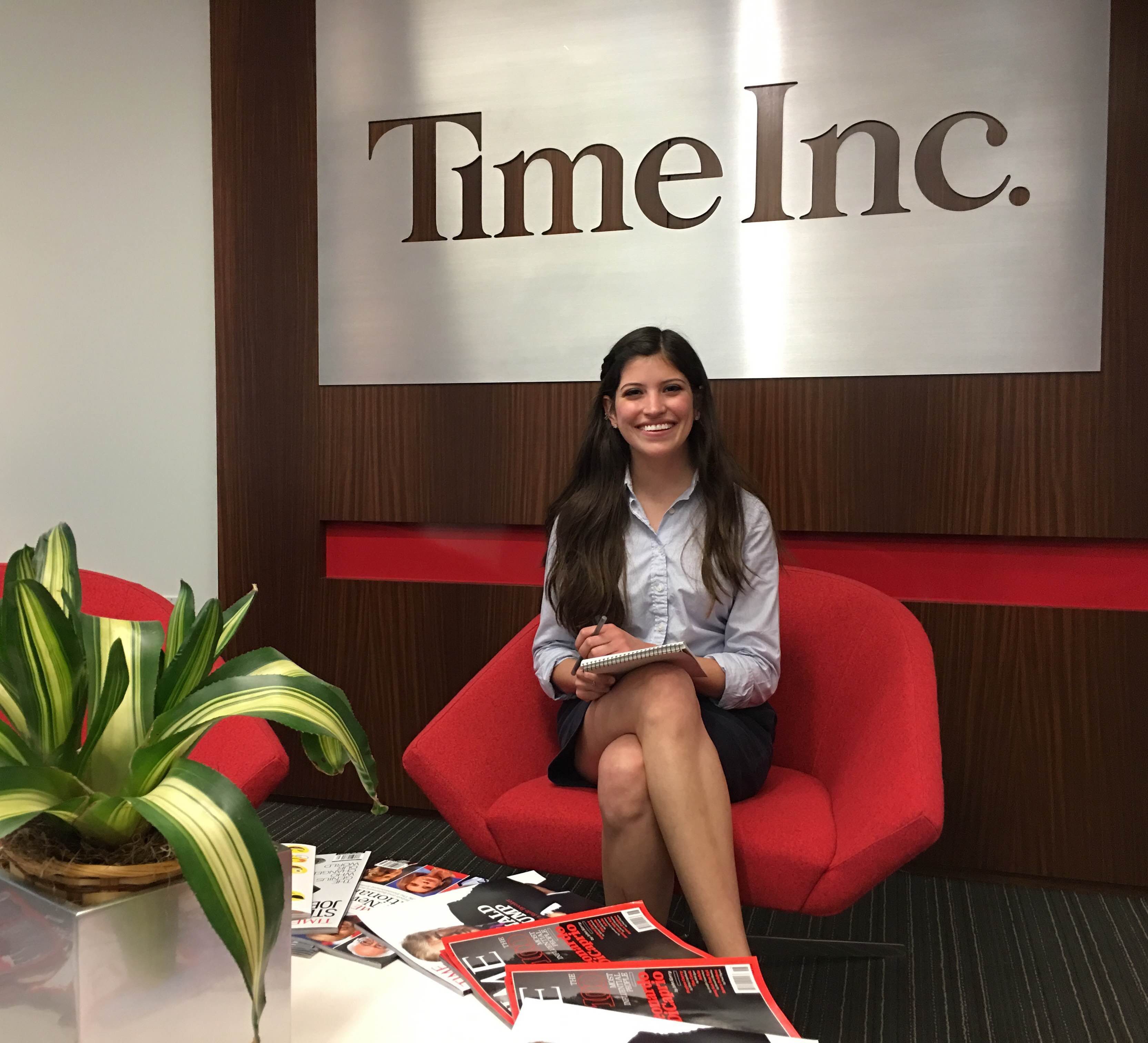 Lissandra Villa sits in a red chair in the lobby of Time Inc.