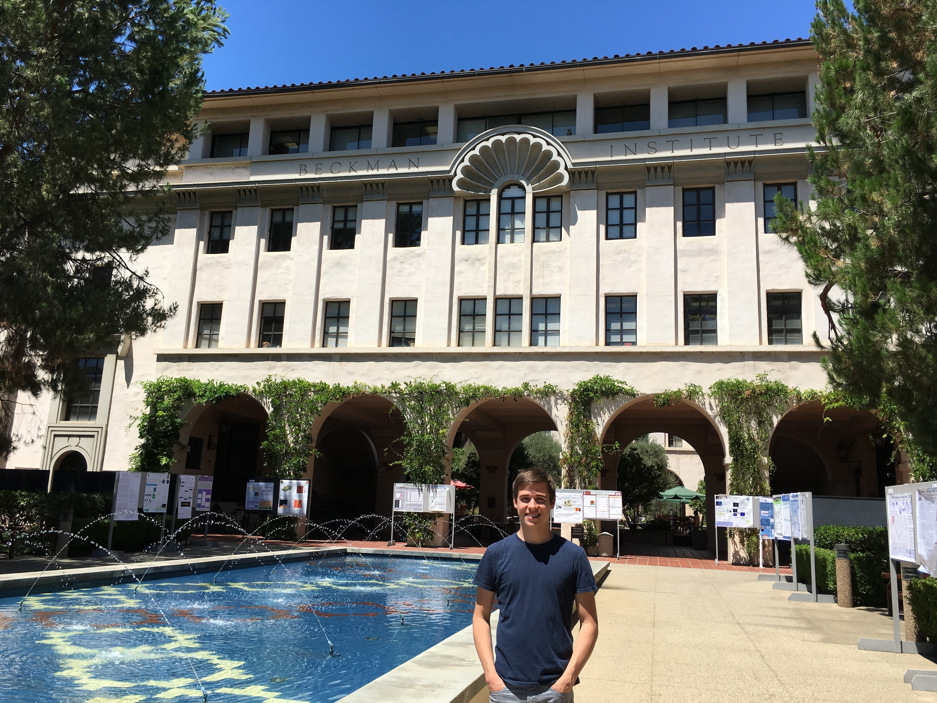 Sam Schulte stands in the foreground of the Beckman Institute building.