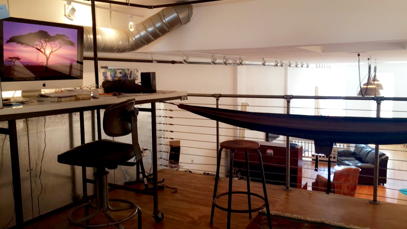 A loft workspace with a large Mac computer and hammock.
