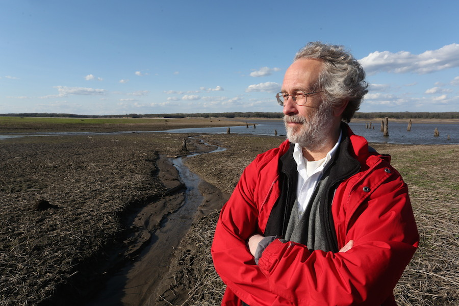 Bill Gutowski stands outside in a red coat by a wetlands area.
