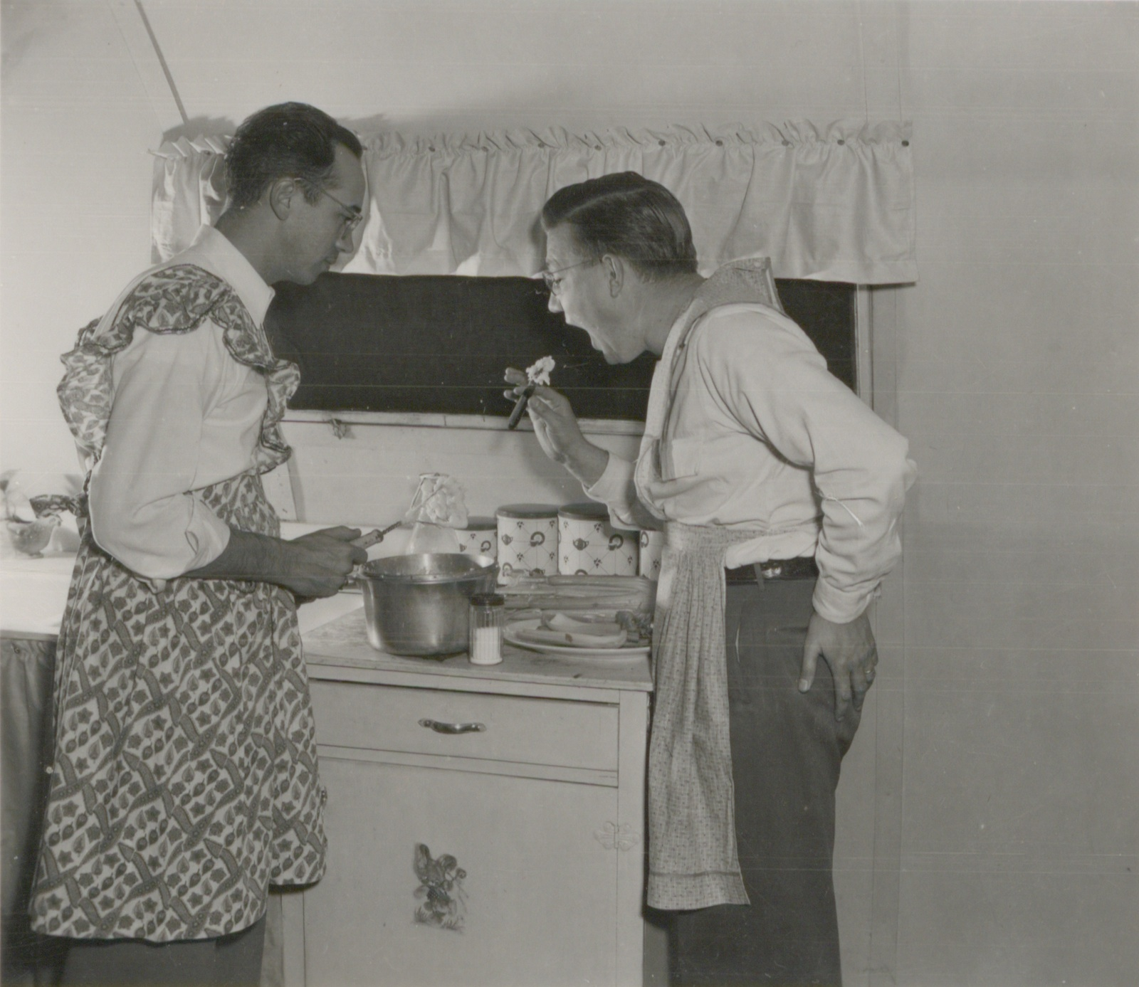 Two men pose for a picture while preparing dinner at Pammel Court.