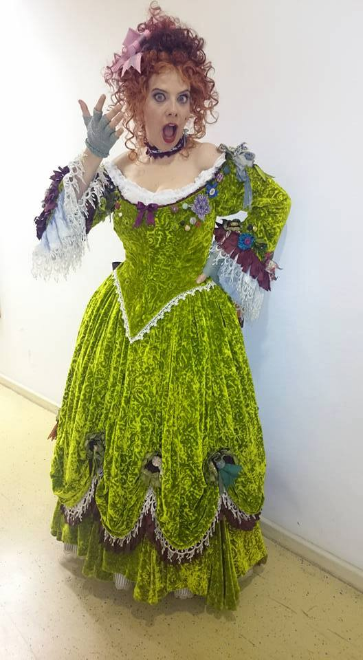 Jennifer Porto in a green dress costume with red curly wig.