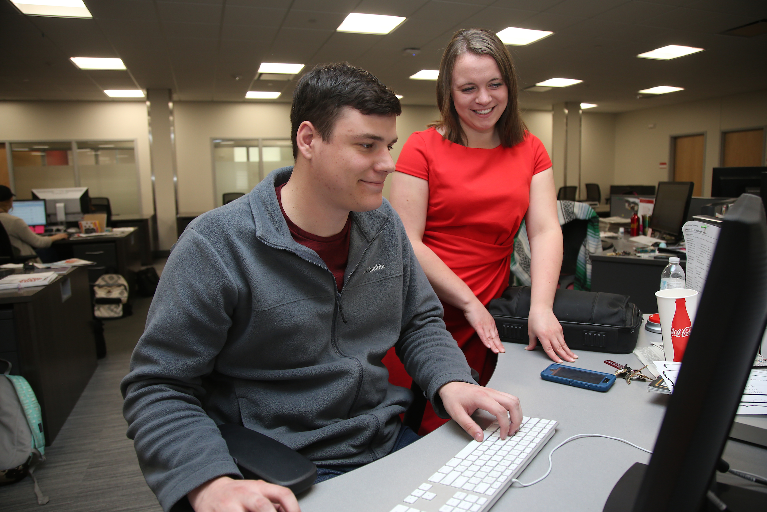 Barske works with Luke Manderfeld, assistant sports editor, on an upcoming story. (Blake Lanser/Iowa State University.)